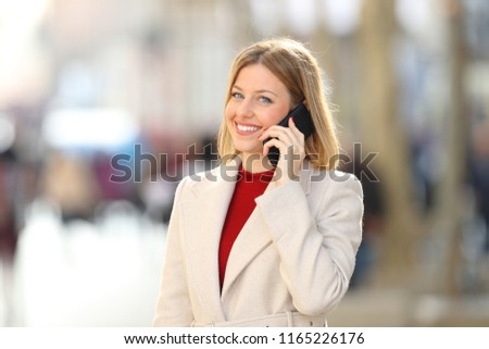 Happy woman having a phone conversation looking at camera in the street in winter #1165226176