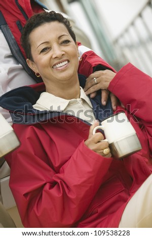 Happy woman having coffee with man's hand on her shoulder
