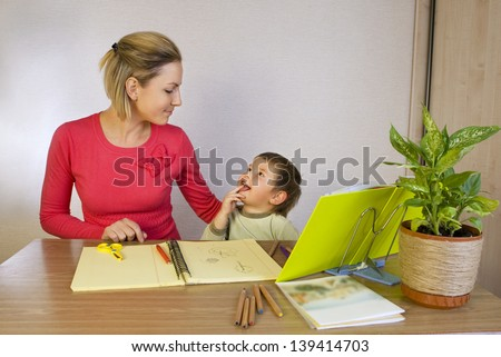 Happy woman helping small kid write