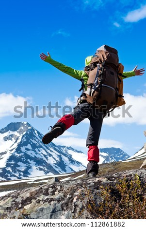 Happy Woman hiking in the mountains, walking and backpacking