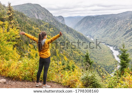 Happy woman hiking up mountain enjoying nature. Landscape with river view from top of trail hike. Girl with open arms outstretched in joy, enjoying travel fall in Jacques Cartier, Quebec, Canada.