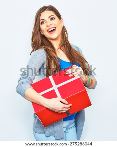 Happy Woman hold gift box. Big smile with teeth. Beautiful female model in studio. White wall background. Red gift box.