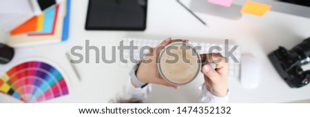 Happy woman holding a cup with latte in a cookie at the workplace in office. Work pleasure concept.