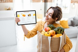 Happy woman holding a digital tablet with launched online store while standing with shopping bag full of fresh products at home. Concept of buying online using mobile devices