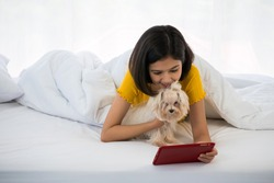 Happy woman holding a tablet and lying on a bed with shihtzu dog