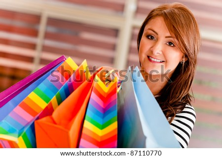 Happy woman holding bags at a shopping center - stock photo