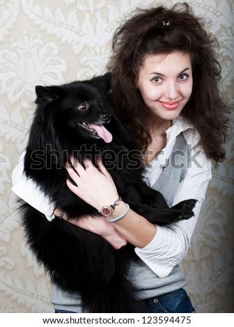 Happy woman holding black dog