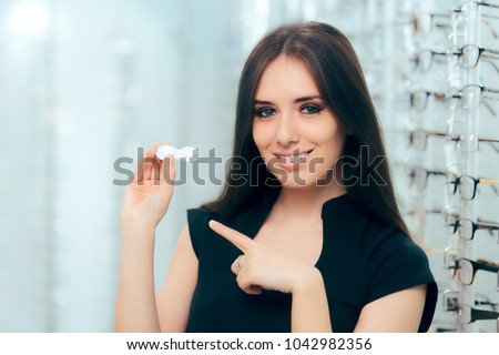 Happy Woman Holding Contact Lenses Case in Optician Store. Female customer choosing contacts over eyeglasses on optical store