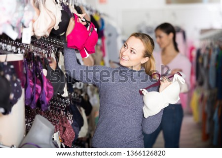 8a94feebe Happy woman holding different brassiere in hands in underwear store   1366126820