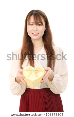 Happy woman holding gift box, isolated on white background