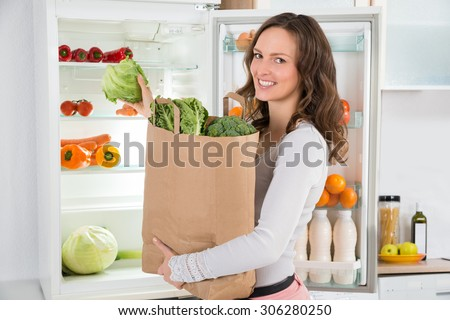Happy Woman Holding Grocery Shopping Bag With Vegetables In Front Of Open Refrigerator
