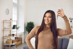 Happy woman holding keys to new home, looking at camera and smiling. Portrait of first time buyer, house owner, apartment renter, flat tenant or landlady. Moving day and buying own property concept