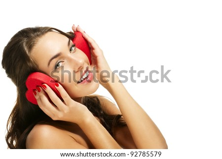 happy woman holding red heart shaped box on her ears on white background