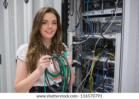 Happy woman holding server wires in data center