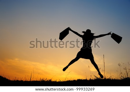Happy Woman holding shopping bags jumping in sunset silhouette