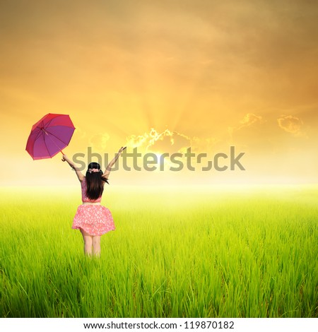 Happy Woman holding umbrella in green rice fields in sunset