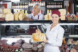 Happy Woman Holding Various Cheese On Board In Store