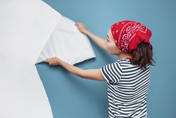 Happy woman housewife peels off an vinyl wallpaper with her hands. The concept of a defect or unsuitable papers when repairing an apartment