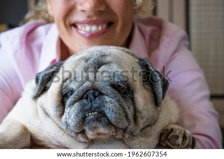 Happy woman hug his dog pug with love and frienship . concept of best friend forever and animal owner enjoying time at home - close up of affection and joyful lifestyle