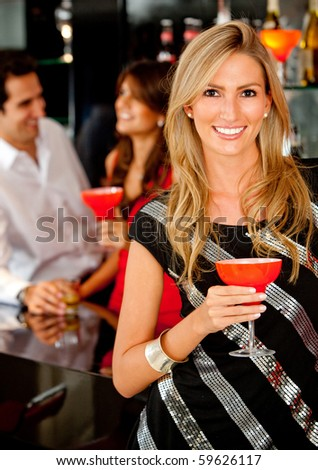 Happy woman in a bar or a nightclub having a drink