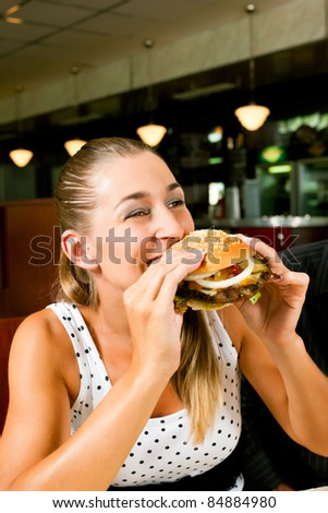 Happy woman in a fast food restaurant eating a hamburger and seems to enjoy it