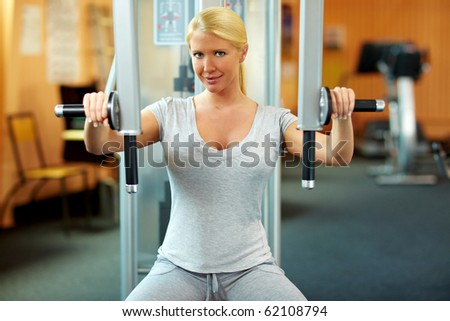 Happy woman in a gym exercising her muscles - stock photo