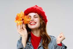 Happy woman in a knitted hat with fallen leaves autumn model