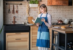 Happy woman in a linen apron standing in the kitchen at the table with a smile leafing through a cookbook