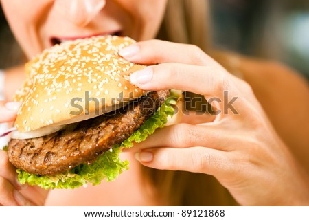 Happy woman in a restaurant eating a fast food hamburger, focus on the burger