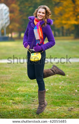 happy woman in autumn scenery in the parc