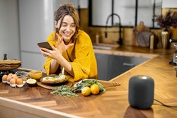 Happy woman in bathrobe controlling home devices with a voice commands, speaking to a smart column during breakfast time on the kitchen at home. Smart home concept