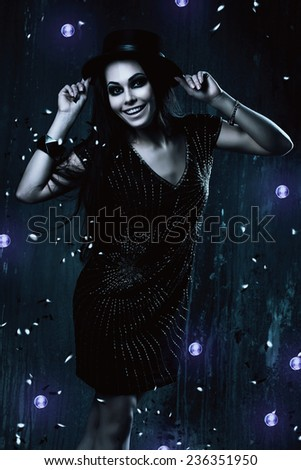 happy woman in black dress with violet lights in dark