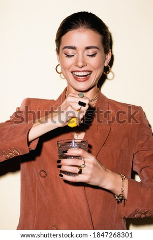 happy woman in brown blazer squeezing lemon in glass with alcohol cocktail on white Stockfoto ©