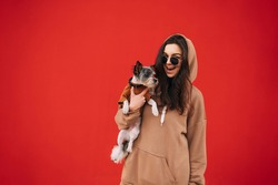 Happy woman in casual clothes isolated on red background with cute dog in hands, looking at camera and smiling. Lady with pet on red wall background.