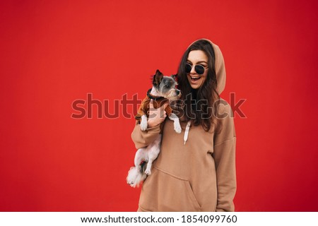 Happy woman in casual clothes isolated on red background with cute dog in hands, looking at camera and smiling. Lady with pet on red wall background. Foto stock ©