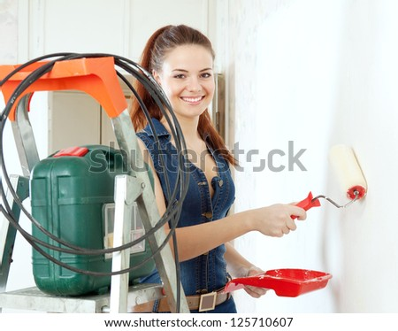 Happy woman in deniums paints wall with roller at home