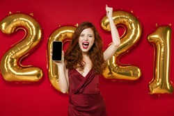 Happy woman in elegant dress hold mobile phone with blank empty screen doing winner gesture isolated on red background, golden numbers air balloons. Happy New Year 2021 celebration holiday concept