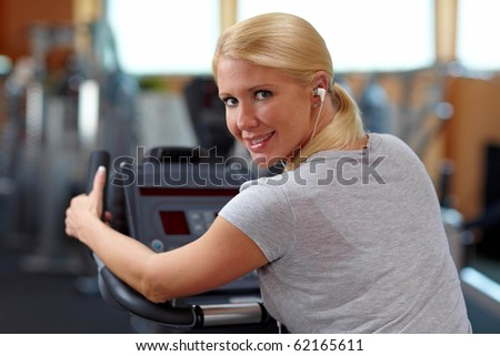 Happy woman in gym on a hometrainer listening to music
