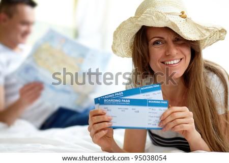 Happy woman in hat showing flight tickets