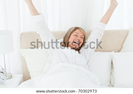 Happy woman in her bed at home