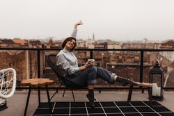 Happy woman in jeans, blue shirt and cool socks rises arm, sits on chair holds coffee cup, smiles on terrace with city view.