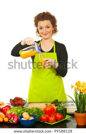 Happy woman in kitchen poured orange juice in glass against white background