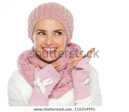 Happy woman in knit scarf, hat and mittens pointing on copy space