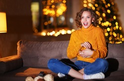 Happy woman in knitted sweater eating popcorn and watching interesting movie while sitting cross legged on sofa in evening at home