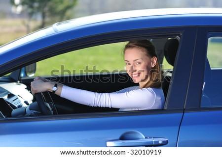 Happy woman in new blue car