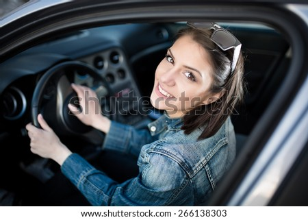 Happy woman in new car, indoor keeps wheel, turning around,smiling.Young woman in car going on road trip.Learner driver student driving car.Driver license exam