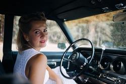 Happy woman in old retro vintage car