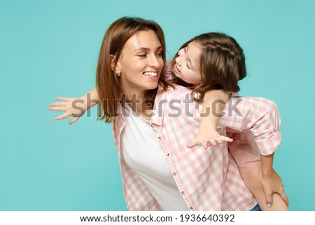 Happy woman in pink clothes have fun with child baby girl 5-6 years old Mommy little kid daughter stand behind hug kiss isolated on pastel blue azure background studio Mother's Day love family concept