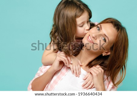 Happy woman in pink clothes have fun with child baby girl 5-6 years old Mommy little kid daughter stand behind hug kiss isolated on pastel blue azure background studio Mother's Day love family concept Stockfoto ©