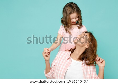 Happy woman in pink clothes have fun with cute child baby girl 5-6 years old Mommy little kid daughter stand behind hug isolated on pastel blue azure background studio Mother's Day love family concept Stockfoto ©